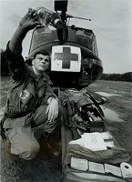 Untitled (Soldier With Medical Supplies On Stretcher In Front Of Helicopter Examining Water, Vietnam)