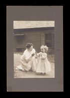 Untitled (unidentified woman kneeling on ground in front of house with unidentifed child, labeled Dorothy Barrette, Agnes Sanborn's mother)