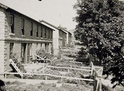 Housing, Industrial: United States. New York. Mineville: Industrial Housing, Row Dwellings of Concrete Block: Witherbee, Sherman & Company, Mineville, New York: Four Family tenement for foreign laborers. Size 70' x 26'. Cellar 70' x 12' x 7'. Slate roof. Cost $3000, or 6¢ per cubic foot. Rent $5.50 per month for each family, including barn. (Houses B Shaft).   Social Museum Collection