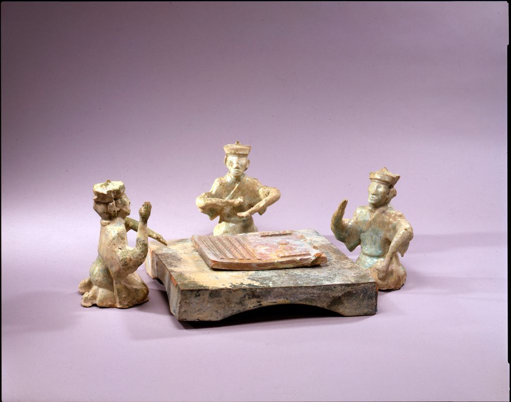Three Capped Men Kneeling Around A Low Table And Playing 'Liubo'