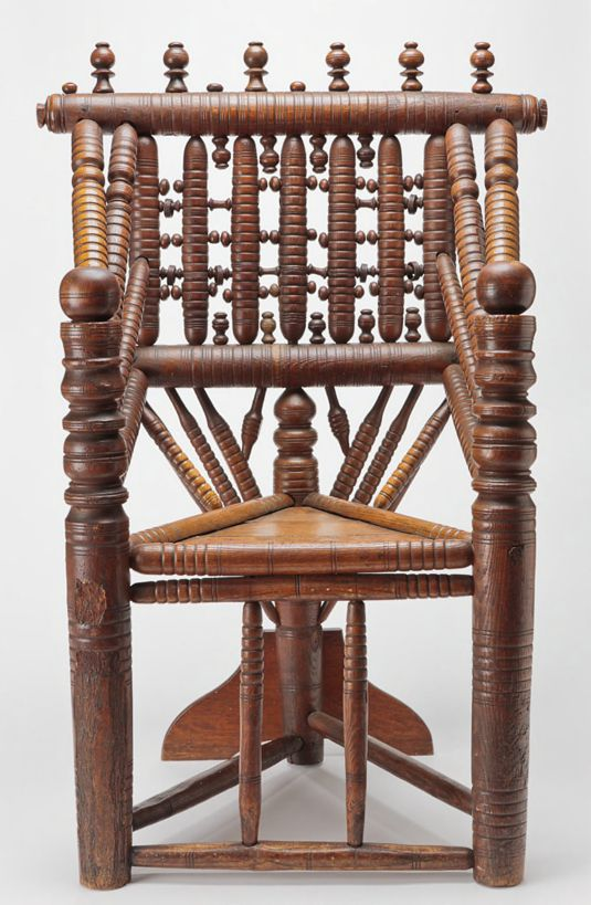 This photograph shows an ornate wooden turned armchair with a triangular seat supported by three legs and reinforced by a wooden fin attached to the back leg. The two front arms of the chair have turned details above seat height and are rounded at top. At the pointed back of the triangular seat are a total of nine carved rods that support the upper back. Four thick spindles connect the upper arms to the backrest. Many rods and roundels make up the back of the chair, which is topped with six vertical elements.