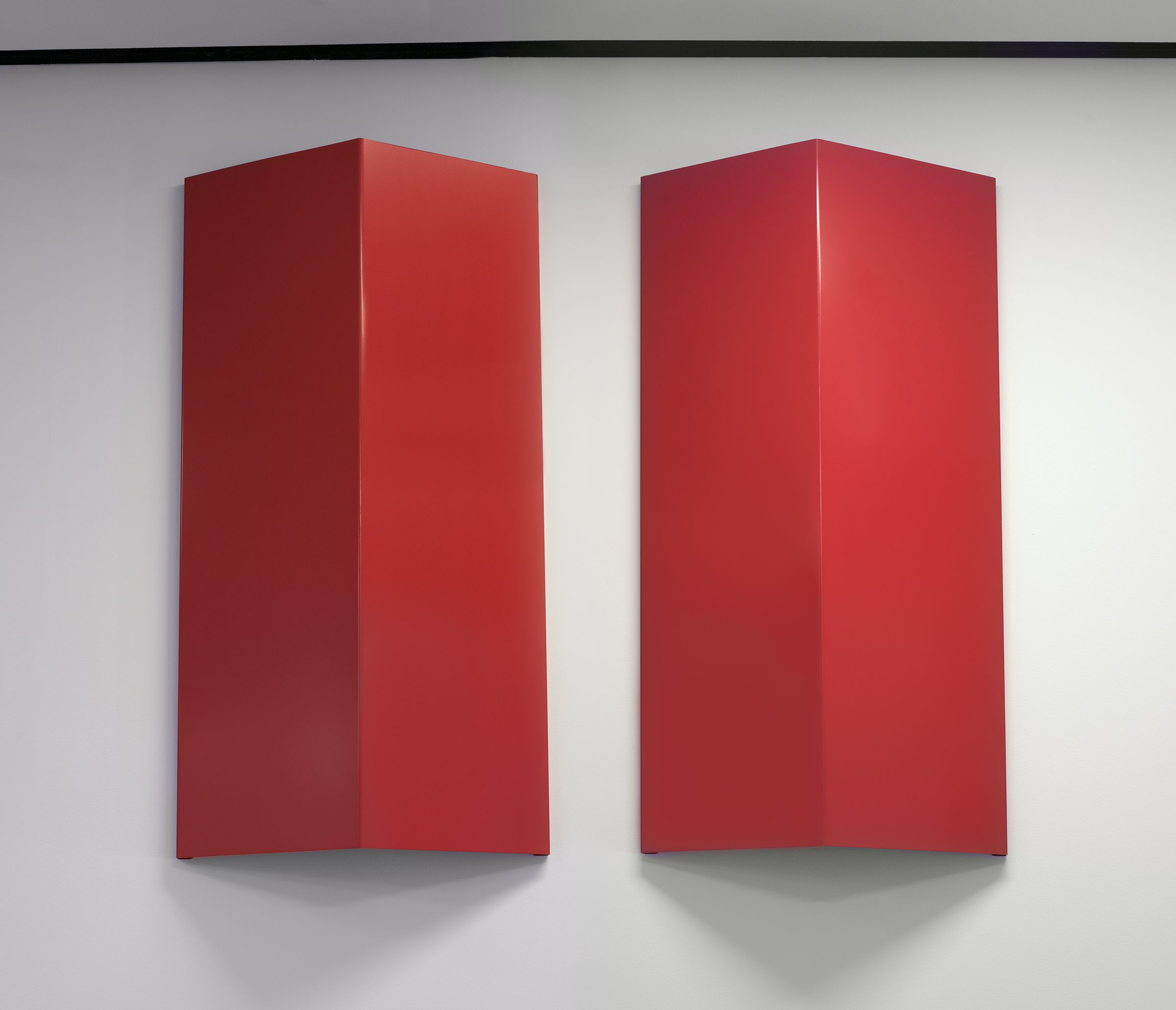 Two identical, bright red-painted aluminum sheets are mounted on a white wall. Each of the rectangular sheets is folded convexly along its center and oriented vertically.