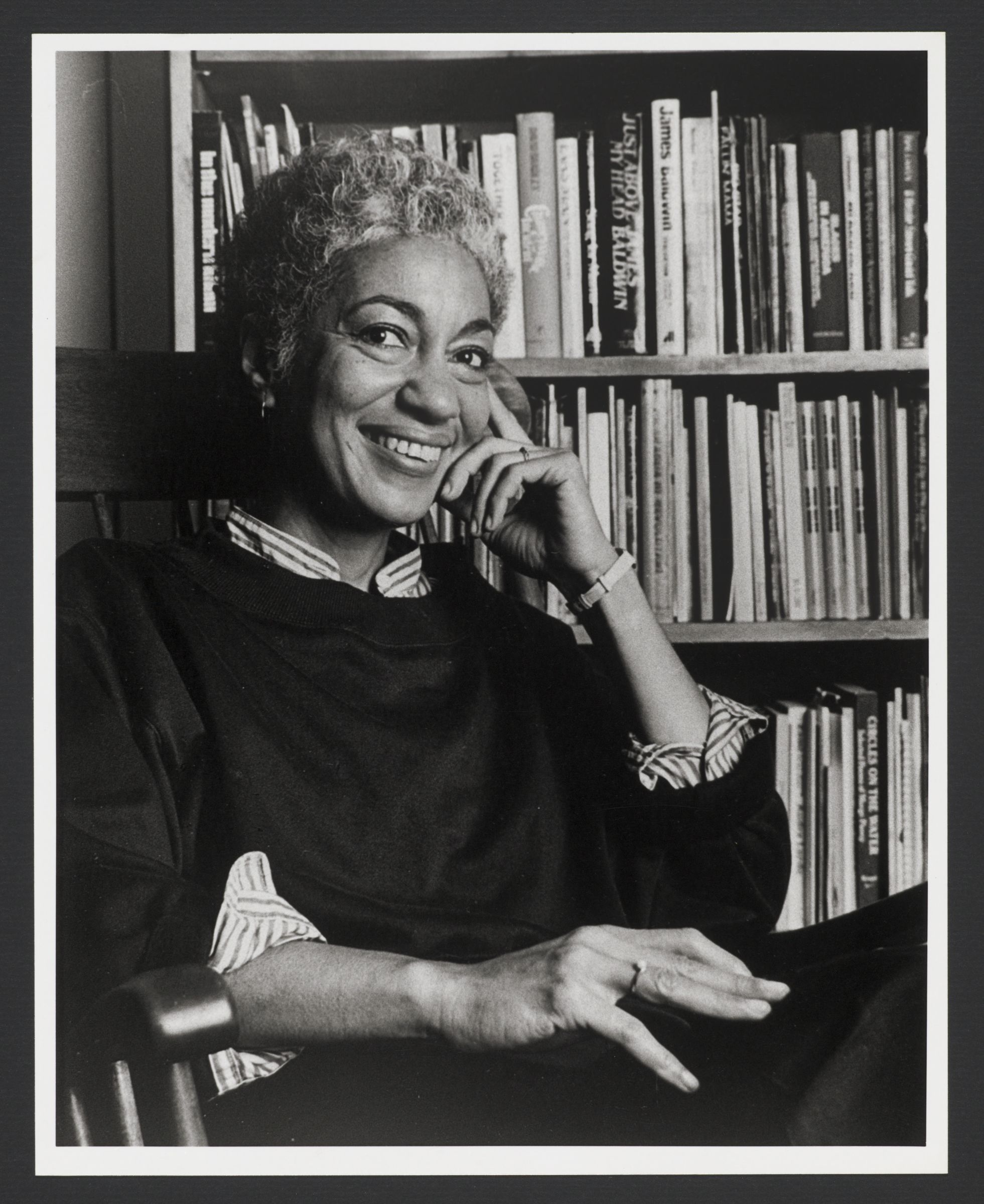 Portrait of June Jordan seated in front of bookcase