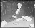 Untitled (Man In Tuxedo Seated At Table With Ashtray, Glasses And Paper)
