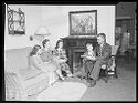Untitled (Family Seated In Living Room With Father Reading Aloud)