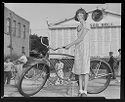Untitled (Girl With Glasses Displaying Bicycle On Town Street With Children In Background)