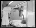 Untitled (Man Adjusting X-Ray Head Over Woman Lying Down Inside Medical Trailer)