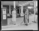Untitled (Man In Uniform And Woman In Plaid Dress Outside Shannon Humble Gas Station)