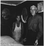 Untitled (older man and woman standing in bedroom with two framed portraits and a poster of Jesus Christ on the walls)
