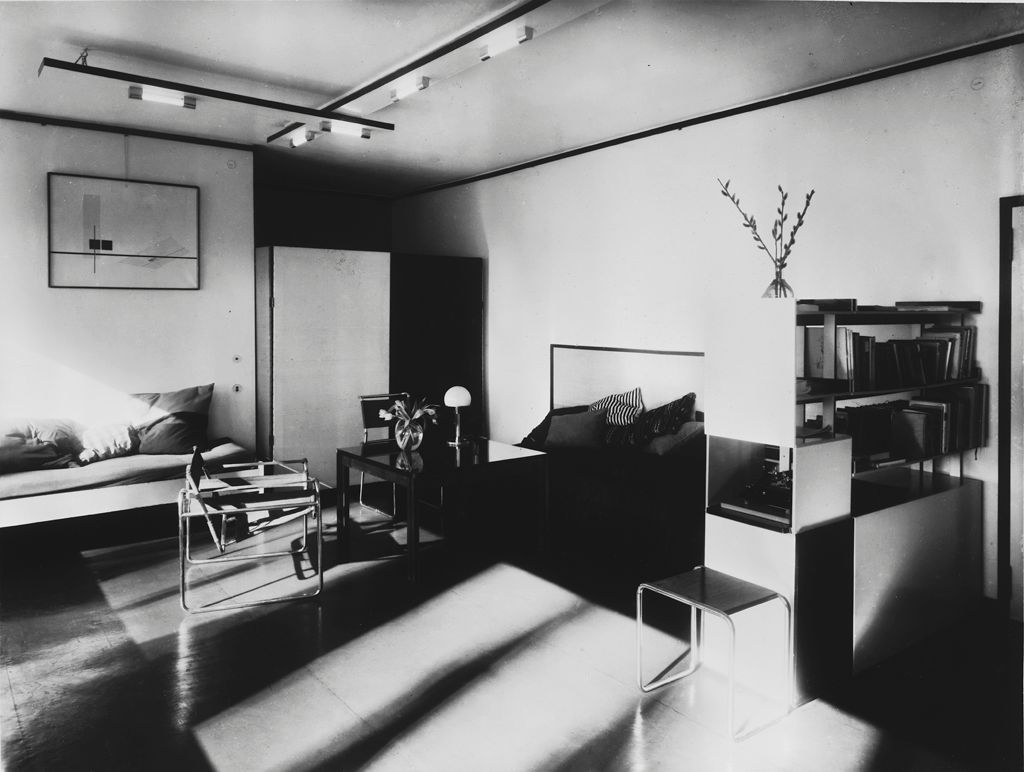This black and white photograph shows a living room filled with sleek, modernist furniture.