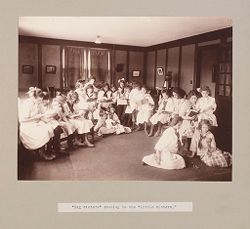 """Charity, Children: United States. New York. Pleasantville. Hebrew Sheltering Guardian Society: Hebrew Sheltering Guardian Society Orphan Asylum, Pleasantville, New York: """"Big sisters"""" reading to the """"little sisters."""".   Social Museum Collection"""