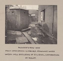 Housing, Conditions: United States. Pennsylvannia. Pittsburgh. Houses; Streets; Yards: Housing Conditions, Pittsburgh, Pa.: Painter's Row: 1909: Privy: open drain: garbage: stagnant waste water..   Social Museum Collection