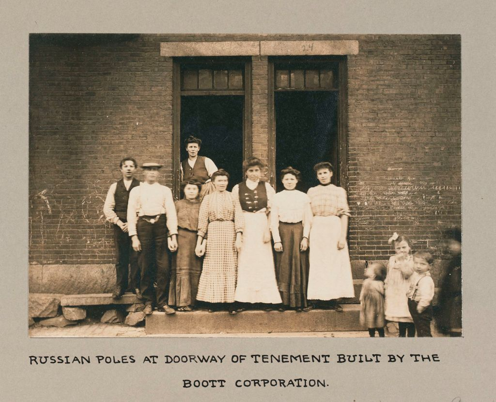 Housing, Conditions: United States. Massachusetts. Lowell. Tenements In French, Greek And Polish Districts: Environment After Immigration, Perpetuation Of European Standards In America: Russian Poles At Doorway Of Tenement Built By The Boott Corporation.