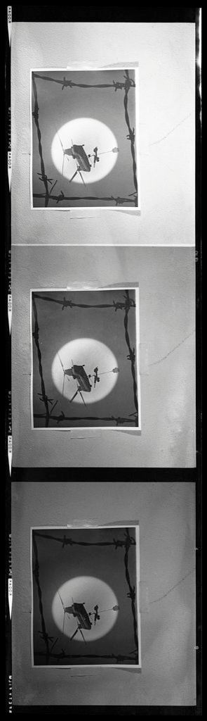 Untitled (Rephotograph Of Image Showing Chinook Helicopter Lifting 105Mm Howitzer Silhouetted Against Sun And Framed By Barbed-Wire Square)