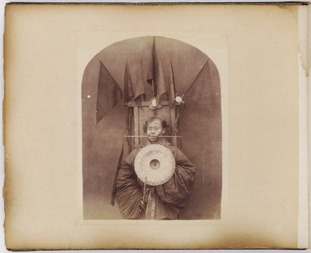 Untitled (Man With Pointed Stick Through Left Cheek, Holding A Metal Disk)