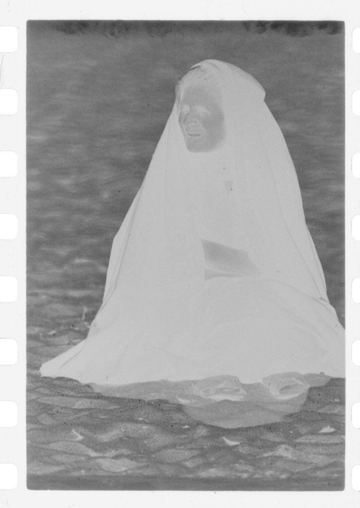 Untitled (Old Woman Wrapped In Shawl Sitting On Beach, Nazaré, Portugal)