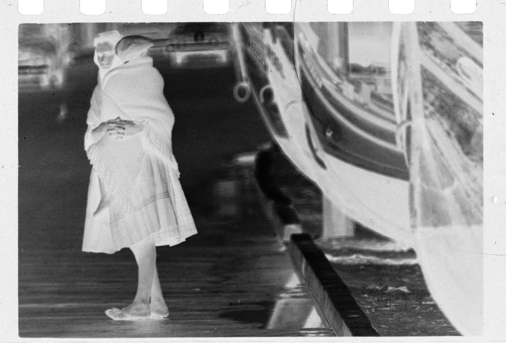 Untitled (Woman Carrying Child Standing In Street Next To Boats, Nazaré, Portugal)