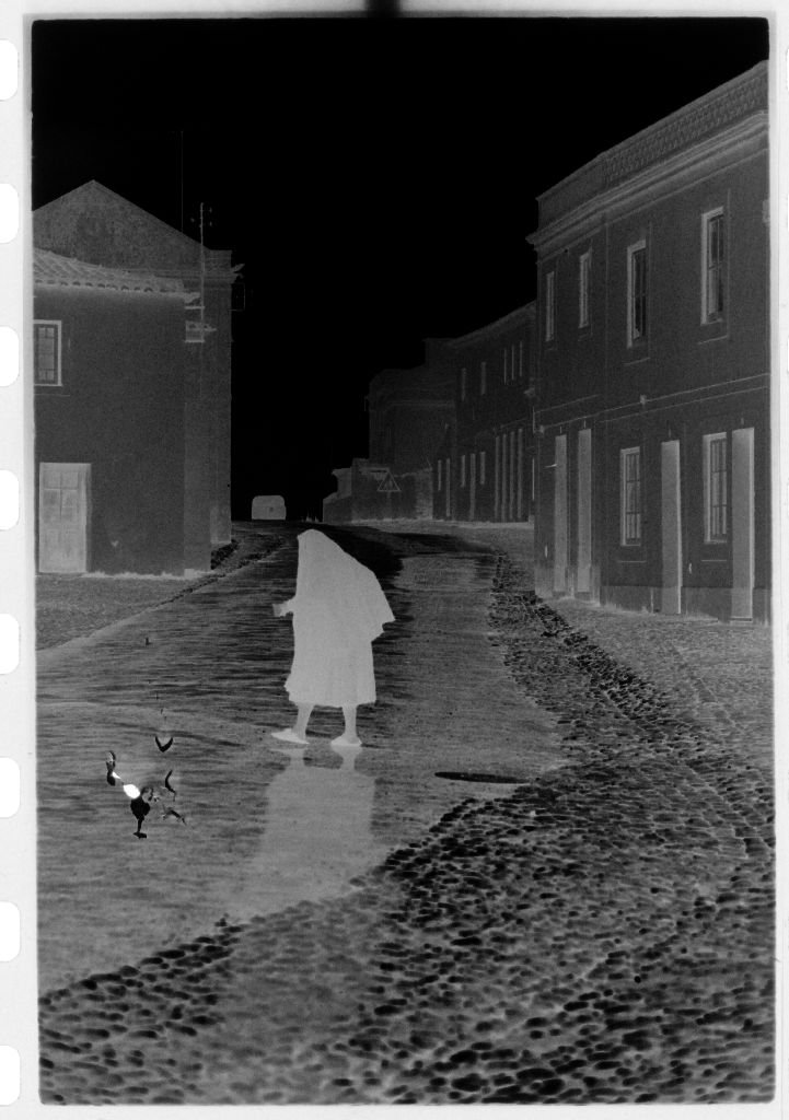 Untitled (Woman Wrapped In Shawl Walking Through Deserted Street, Nazaré, Portugal)
