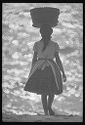 Untitled (Woman Carrying Basket On Her Head Walking Along Beach, Nazaré, Portugal)