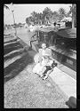 Untitled (Young Girl And Woman Sitting On Ledge In Front Of Boat)
