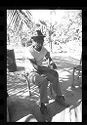 Untitled (Man In White Shirt And Fedora Sitting On Chair Beneath Palm Tree)