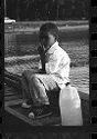 Untitled (Boy Sitting On Dock Next To Jug Of Water)