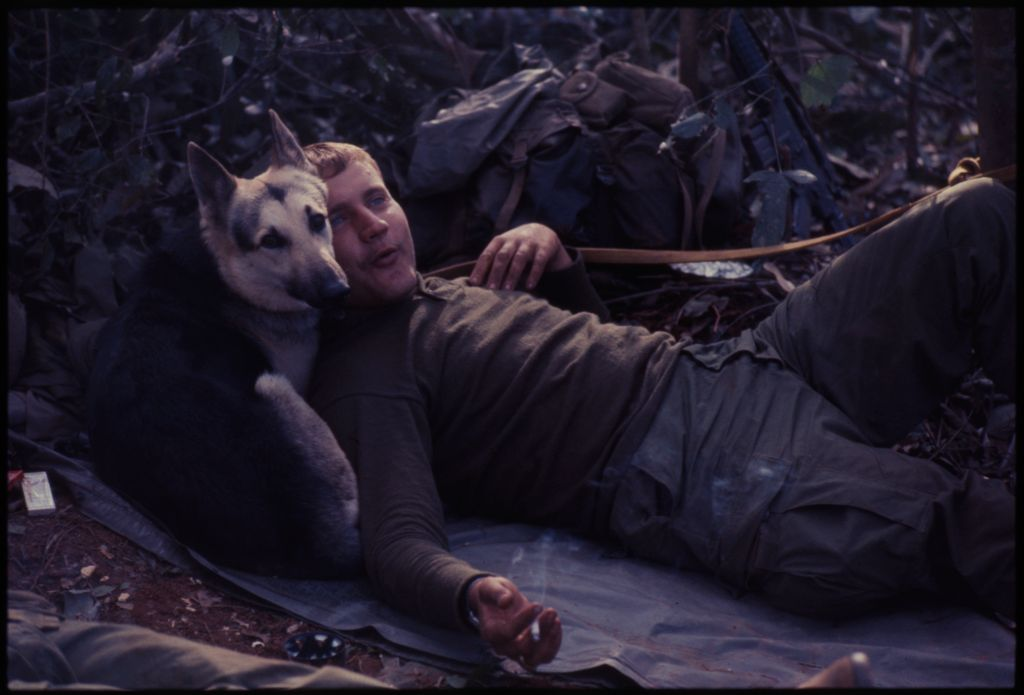 Untitled (Soldier Resting On Ground With Dog Laying Down Behind His Shoulders, Central Highlands Near Dak To, Vietnam)