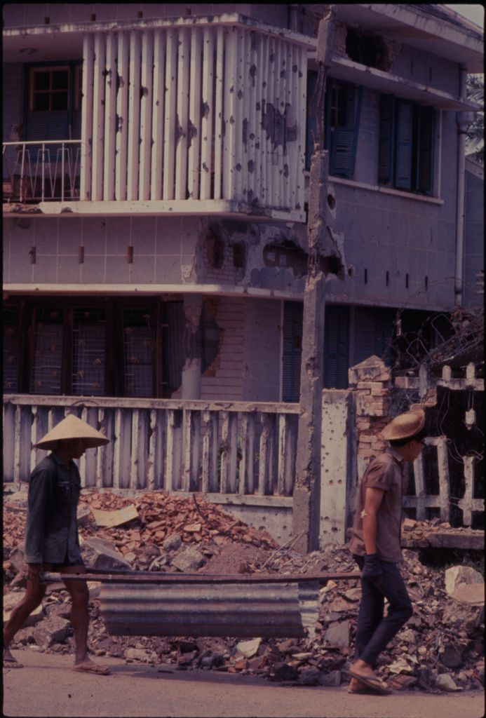 Untitled (Two Men Carrying Metal Trough To Pick Up Rubble In Front Of Buildings Damaged During The Tet Offensive, Hue, Vietnam)