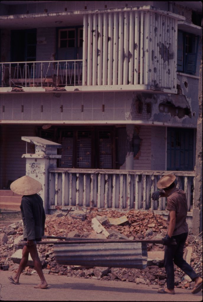 Untitled (Men Carrying Metal Trough Away From Rubble Pile, Hue, Vietnam)
