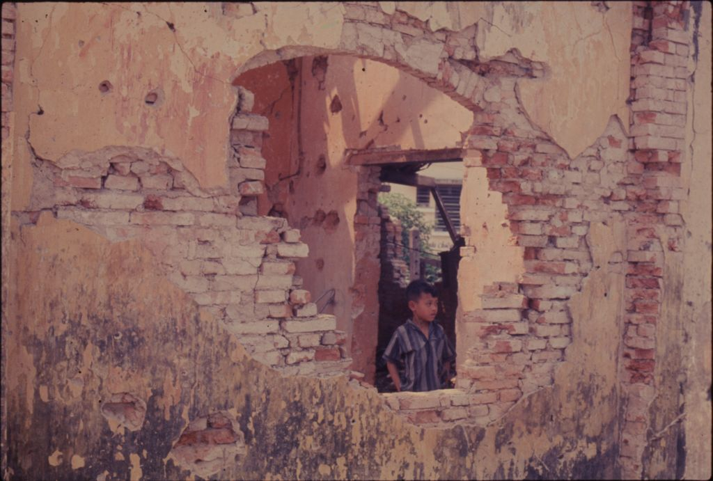 Untitled (Young Boy Standing Inside Damaged Building Visible Through Hole In Wall, Hue, Vietnam)