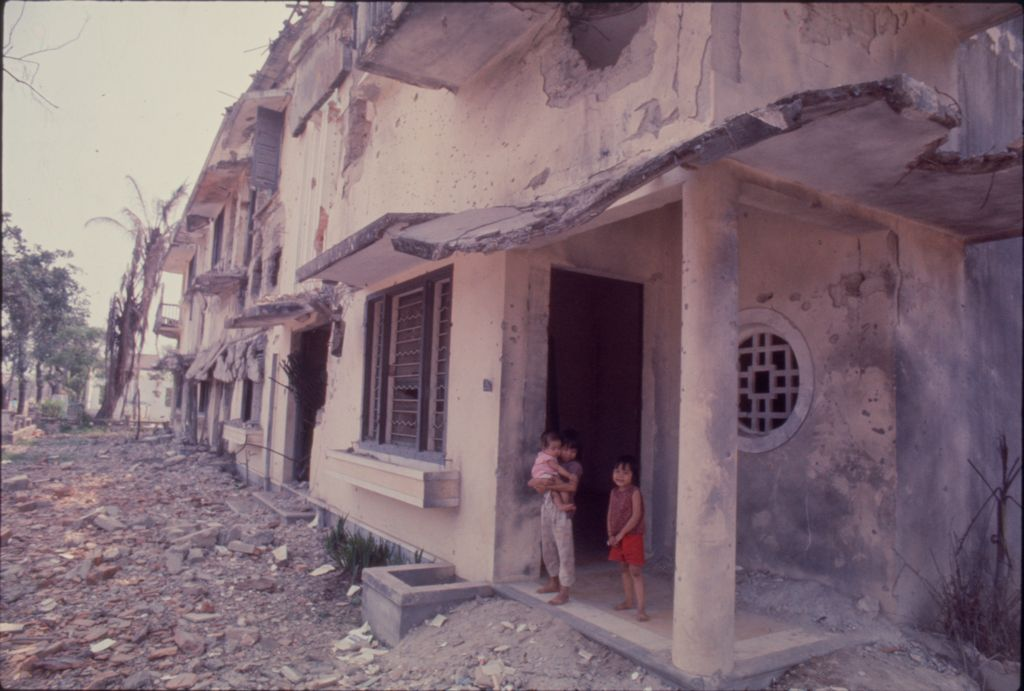 Untitled (Three Young South Vietnamese Children Outside Damaged Building On Debris-Filled Street, Hue, Vietnam)