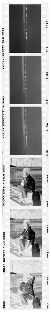 Untitled (Boy Sitting On Dock Next To Jug Of Water; View From A Distance Of Boats On Water)