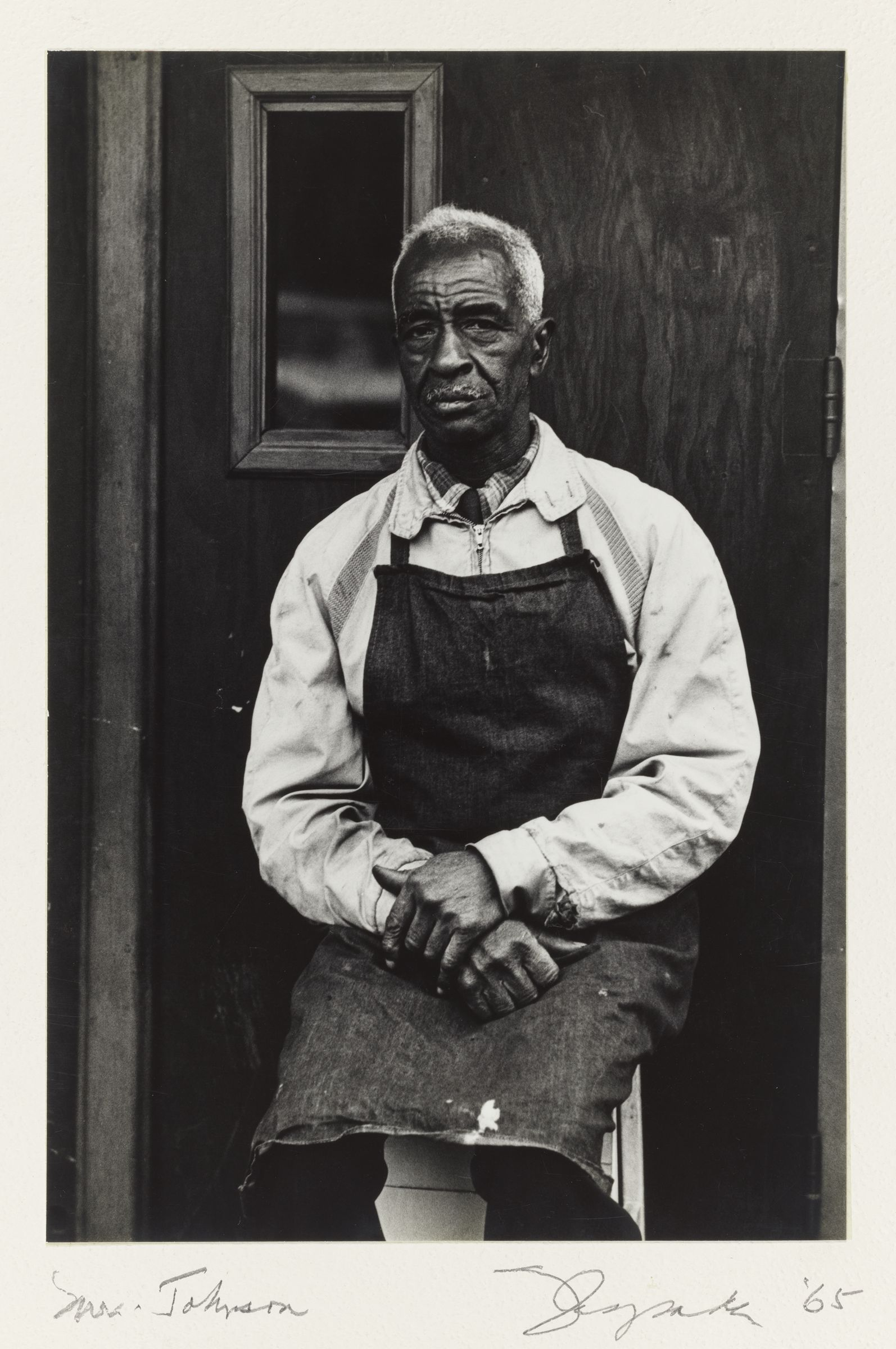 """A black and white photograph shows an older man with white hair and dark skin seated in front of a wooden door with a small rectangular window. He is wearing a light-colored zip-up jacket and a dark-colored apron. He stares directly at the viewer, his large hands folded neatly on his lap. """"Mr. Johnson,"""" """"'65,"""" and the artist's signature are scribbled in the bottom margin of the photograph."""