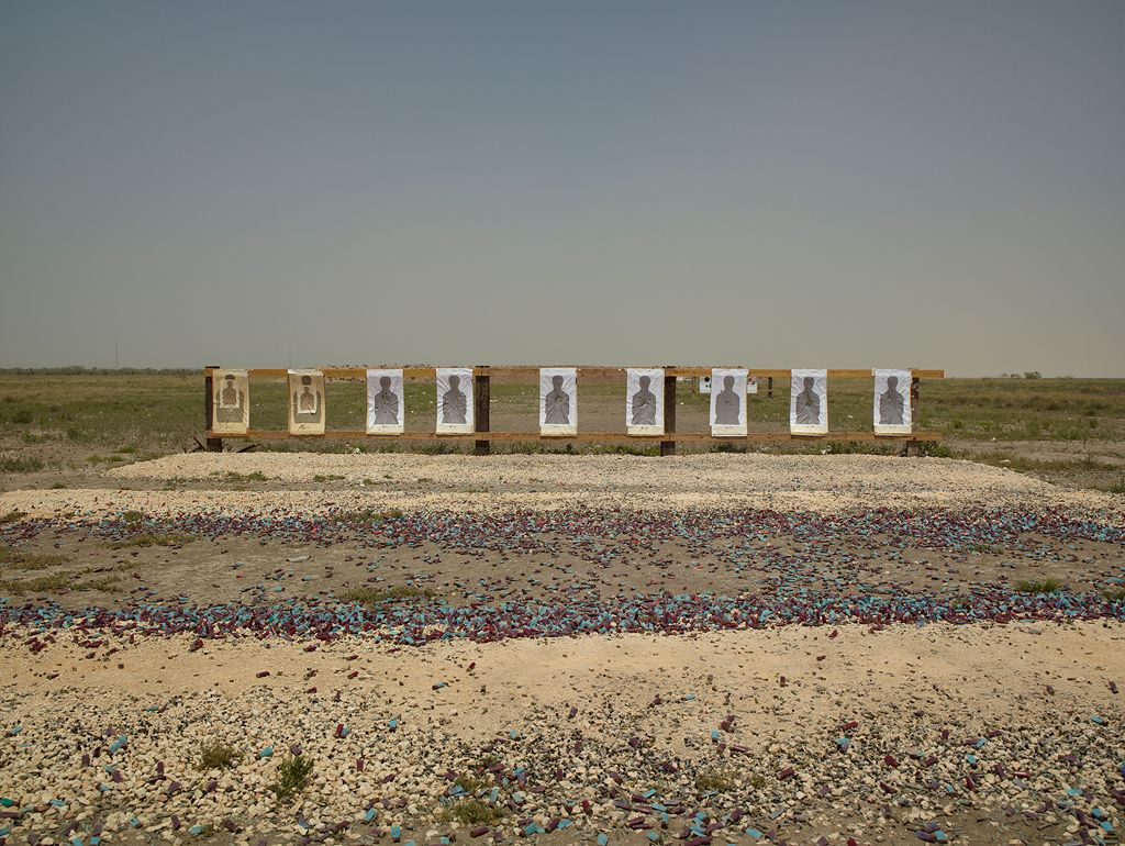A color photograph captures a target range in a desert landscape. A row of nine targets aligns with the horizon. Each features a human figure silhouetted in dark gray. In the foreground, thousands of dark red and turquoise shell casings are scattered amid the dusty beige rocks and pebbles of the desert earth, while grasses in shades of brown, yellow, and green fill the middle ground. An open sky in shades of hazy blue provides a backdrop for the scene.