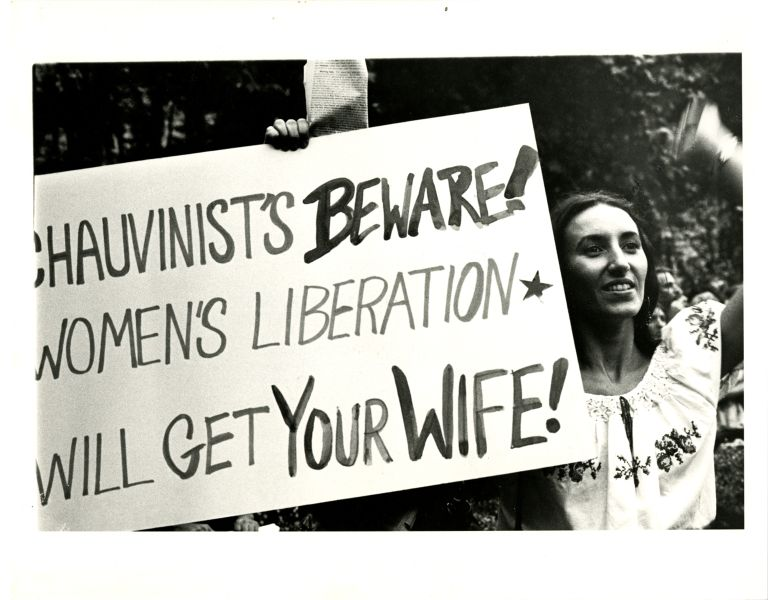 Woman holding poster at women's rights demonstration.