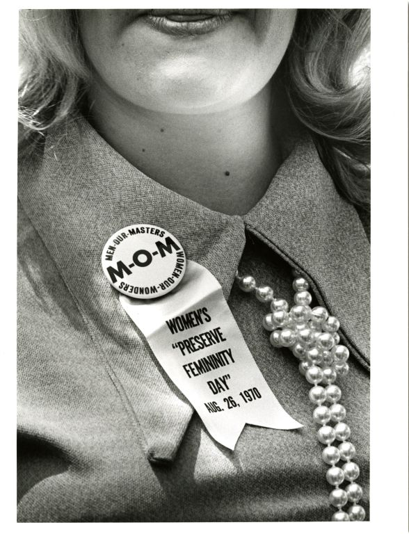 """Anti-woman's rights demonstrator wearing a button reading """"Men our masters, MOM"""" with the Women's """"Preserve Feminity Day,"""" August 26, 1970."""