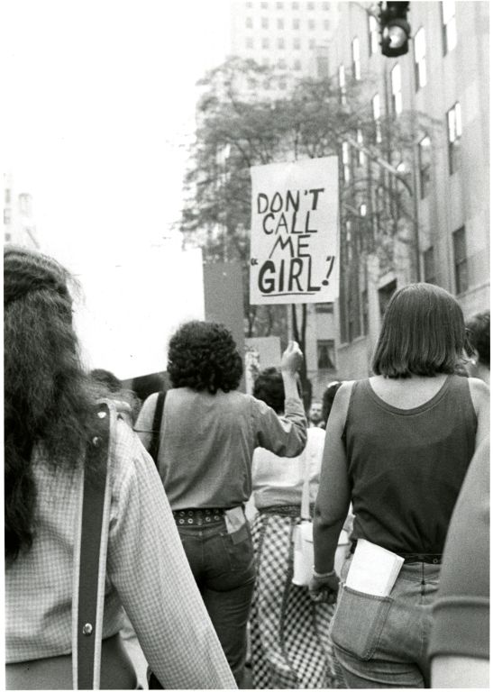"Women marching at a women's rights rally carrying sign reading ""Don't call me girl"""