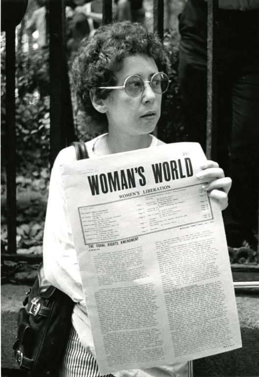 "Woman holding a copy of ""Woman's World: Women's Liberation"""