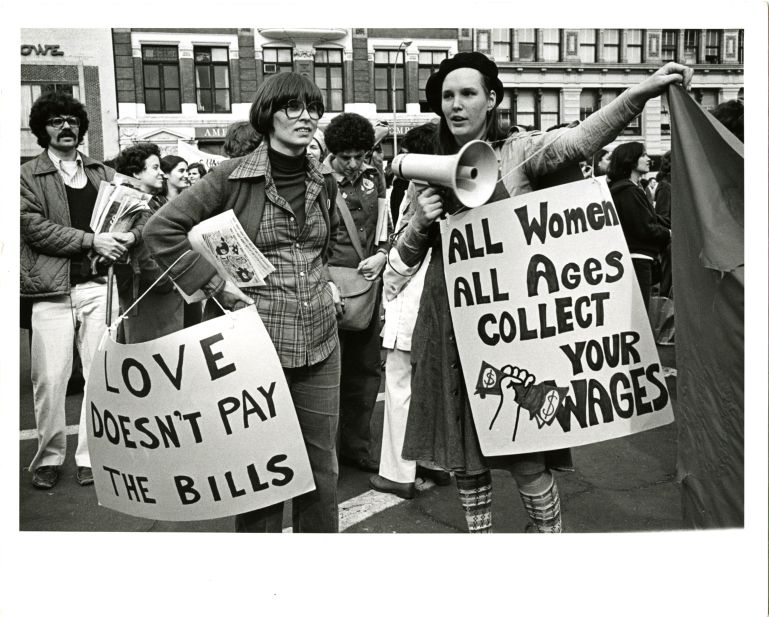 "Marchers at International Women's Day rally holding signs reading ""Love doesn't pay the bills"" and ""All women all ages collect your wages"""