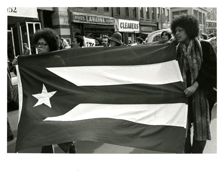 Women marchers with Puerto Rican flag at International Women's Day