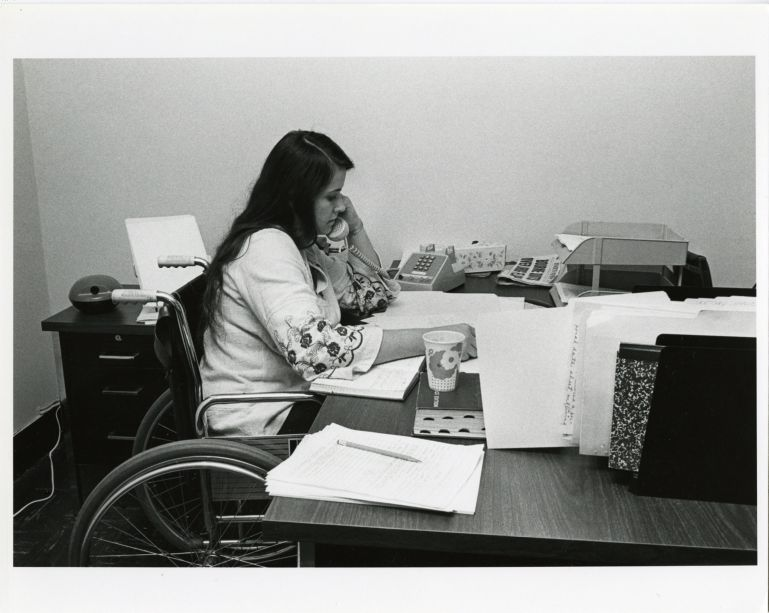 Woman in wheelchair working at a desk at the National Paraplegia Foundation