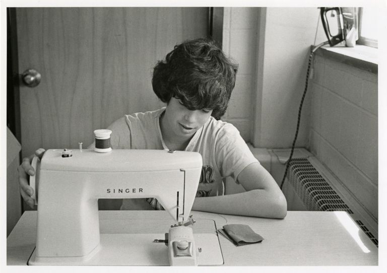 High school home economics student sitting with a Singer sewing machine