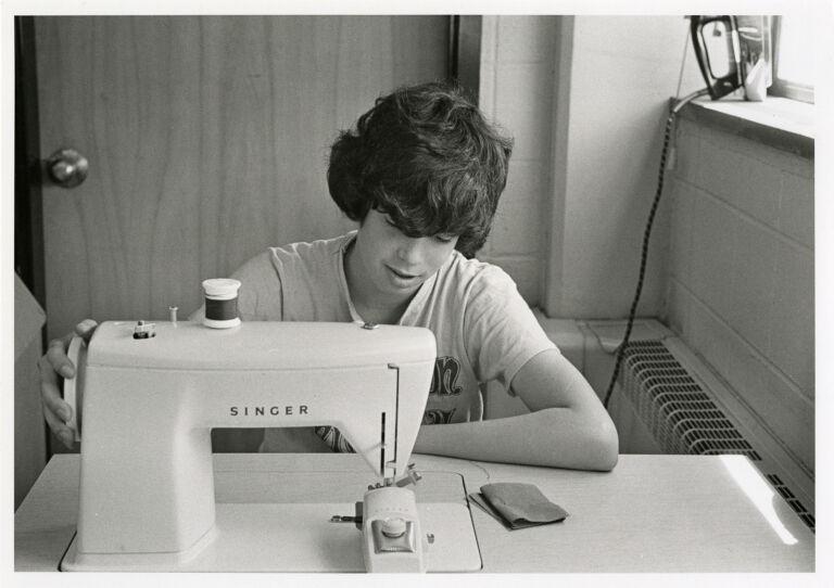 High school classes: boy using sewing machine