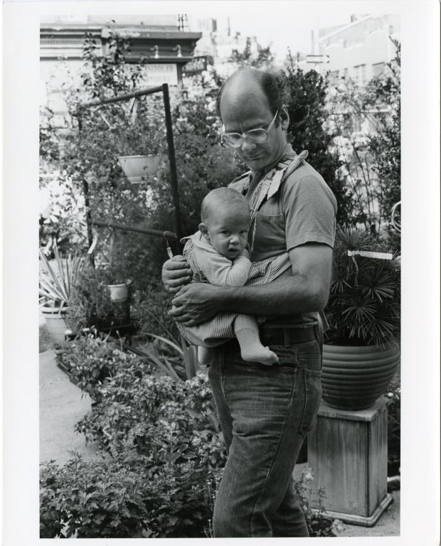 Father carrying infant in carrier.