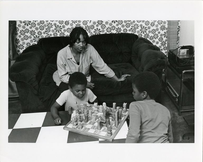 Mother teaching sons to play chess.