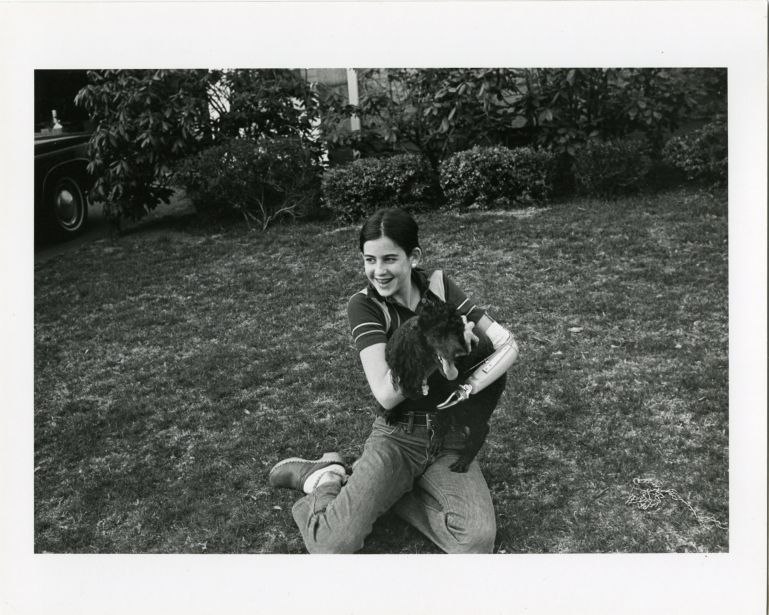 Portrait of teenage girl with artifical arm holding dog