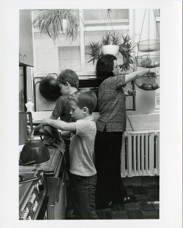 Boys doing dishes with their mother in an apartment kitchen