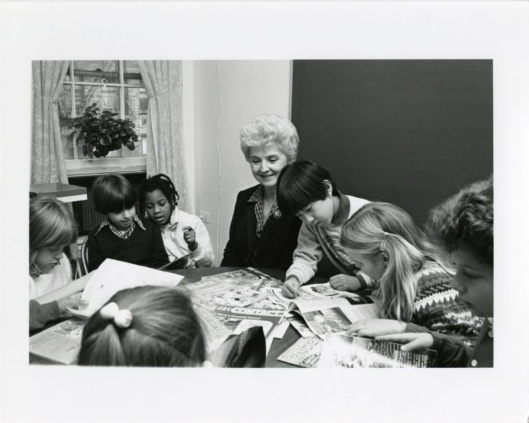 Bernice E. Cullinan with a group of children reading around a table