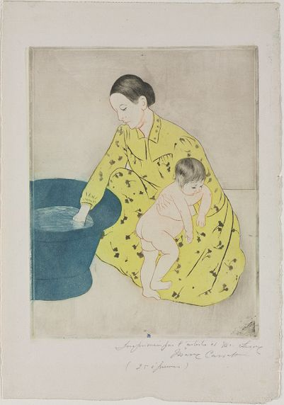 A woman kneels in front of a round blue water filled tub, holding onto a toddler in her left arm.