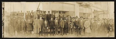 Panoramic portrait of an unidentified group of men, including Roscoe Simmons, standing in the front row, wearing a Homberg hat and holding a cane Digital Object